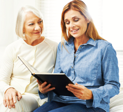 elderly woman and caregiver reading book