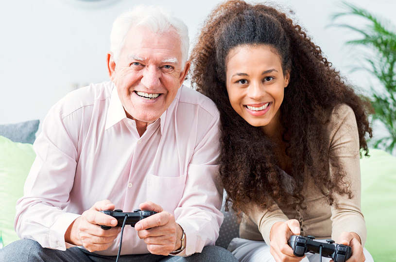 caregiver and elderly man playing games